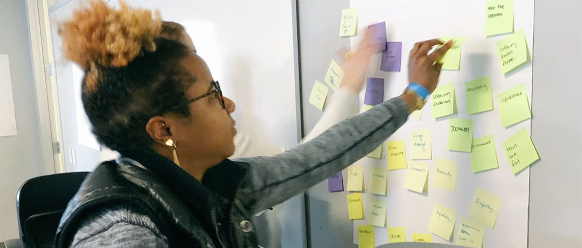 A woman putting post-it notes on a board